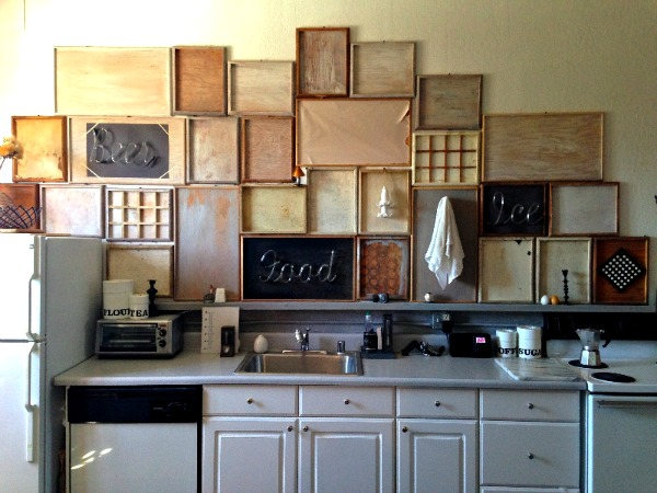 Display wall of vintage trays and neon letters in kitchen