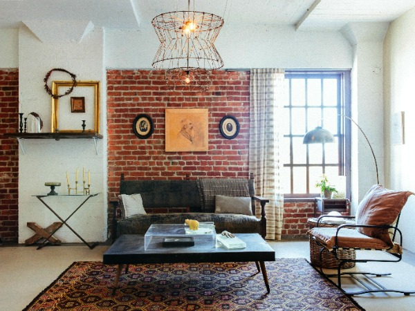 Warehouse apartment living room with exposed brick wall and retro furniture