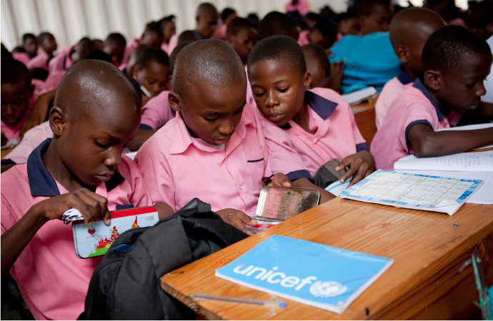 Boys at school in Haiti with unicef exercise books